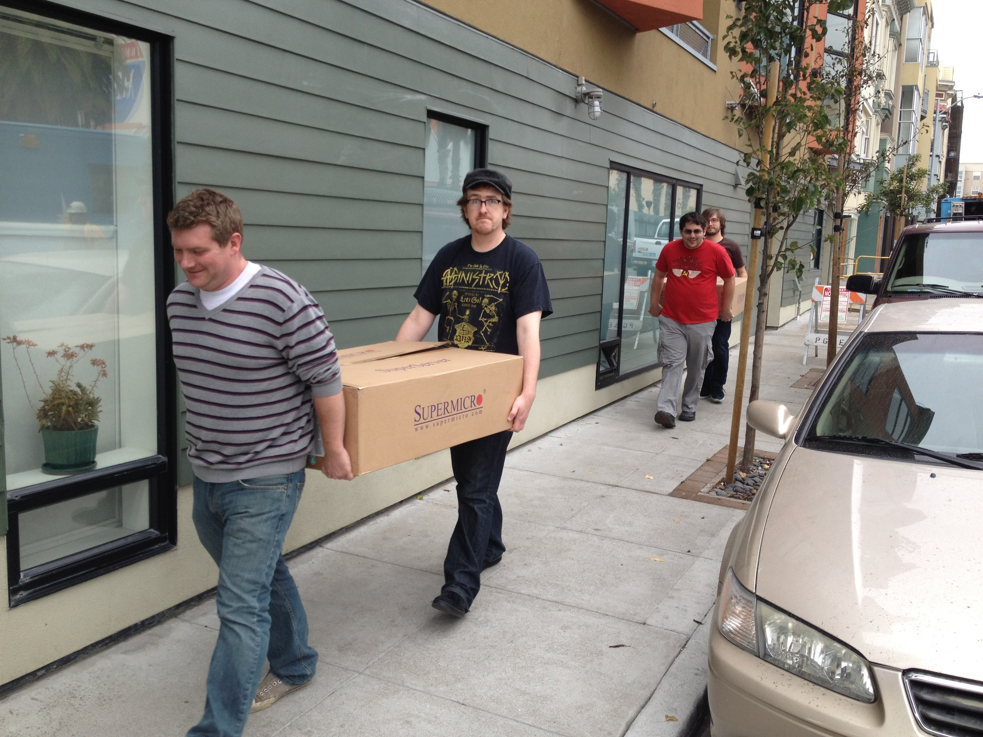 Simon Wistow and Patrick McManus carry a box across the street to Fastly's new office.