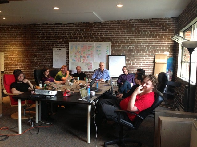 A small and mighty team of <10 gather for a meeting in an early Fastly office.